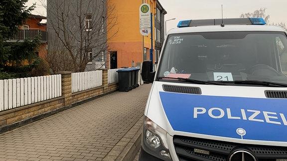 Ein Polizeiwagen steht vor einem orangefarbenen Gebäude.
