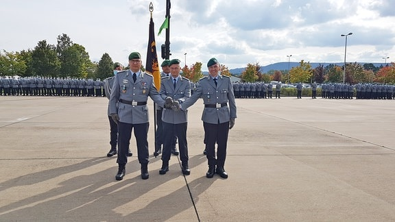 Der alte und der neue Kommandeur des Panzergrenadierbataillons 391, Oberstleutnant Rouven Habel und Oberstleutnant Dominik Schellenberger stehe gemeinsam mit dem Kommandeur der Panzergrenadierbrigade 37, Oberst Alexander Krone, vor einer Truppenfahne.