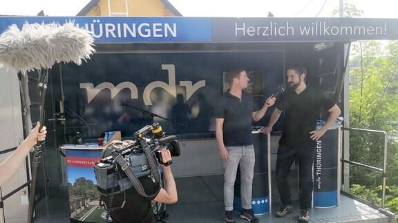 Ein Mann gibt einem Moderator ein Interview.