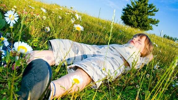 Ein Kind liegt mit geschlossenen Augen auf einer Bergwiese.