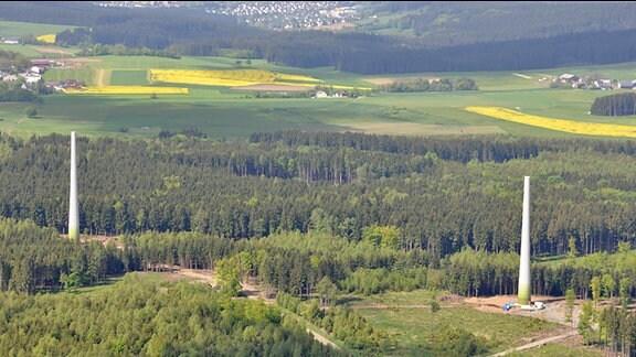 Luftbildaufnahme zweier noch nicht fertig gestellten Windräder. Zu sehen sind die Rümpfe ohne Rotorblätter. Die Windräder stehen in einem Waldgebiet in der Nähe mehrerer Ortschaften.