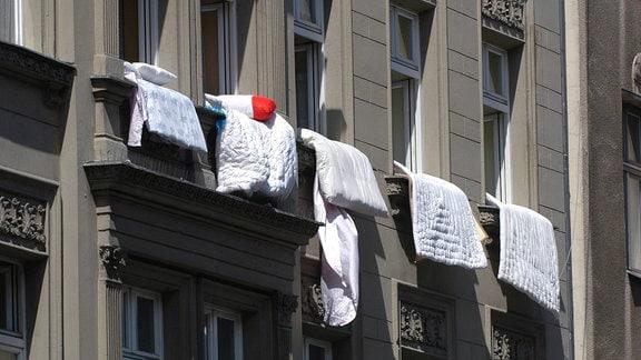 Bettwäsche hängt aus geöffneten Fenstern.