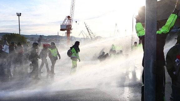 Polizei setzt Wasserwerfer gegen demonstrierende Hafenarbeitern ein.
