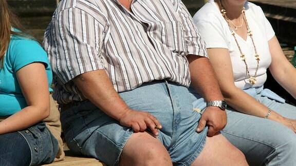 übergewichtige Familie, auf einer Bank sitzend
