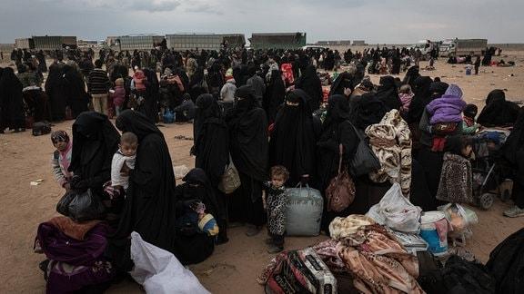 Mitglieder der kurdischen YPG bringen Frauen und Kinder von IS-Dschihadisten in Trucks aus Baghoz weg.