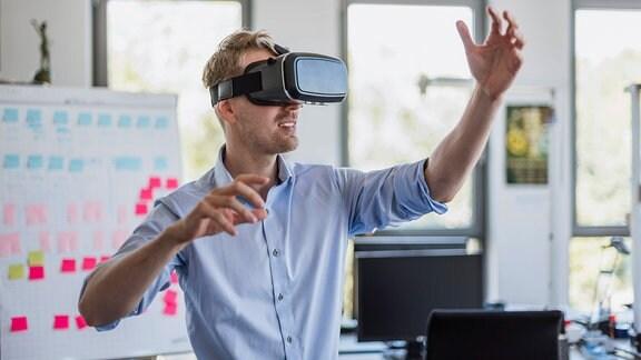 Mann in Büro trägt VR-Brille