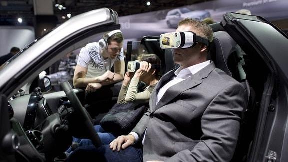 Zwei Männer sitzen im Auto mit einer VR-Brille.
