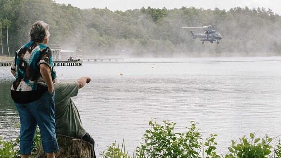 Anwohner beobachten Hubschrauber der Bundespolizei beim Wassertanken nahe Lübtheen in einem Badesee.