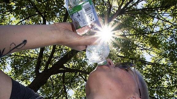 Sommer im Siegerland, eine Frau steht im Schatten eines Baumes und trinkt Wasser aus einer Flasche, die Sonne scheint vom blauem Himmel durch den Baum.