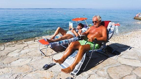 Ein Paar sonnt sich auf Liegestühlen am Wasser
