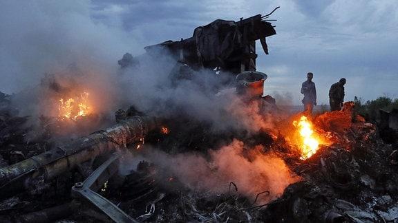 Flammen lodern in den Trümmern des Passagierflugzeugs MH 17.