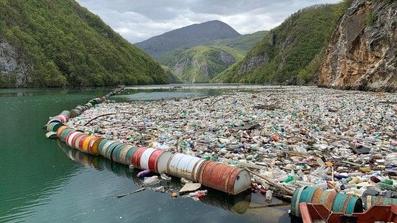 Müll treibt in einem Fluss vor Bergpanorama.