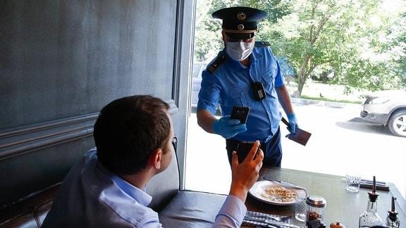 Ein Mitarbeiter der Stadt Moskau liest bei einer Razzia in einem Brooklyn Pizza Pie restaurant.