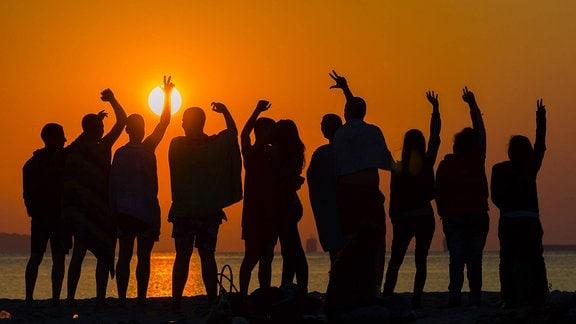 Menschen feiern 2015 den Sonnenaufgang des 1.Juli am Strand von Varna