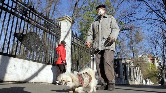 Alter Mann mit Mundschutz führt Hund Gassi in Dnipro, Zentralukraine.