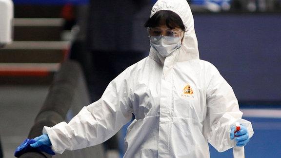 Mitarbeiterin bei der Desinfektion eines Geländers