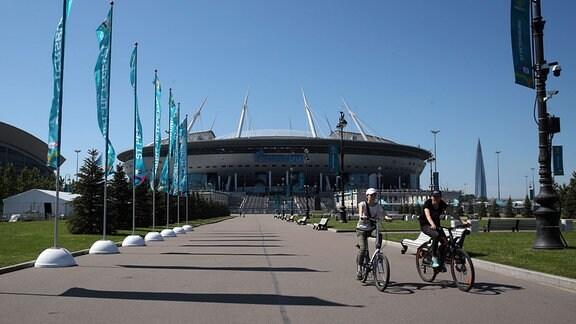 Zwei Radler fahren vor der Gazprom Arena in Sankt Petersburg
