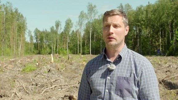 Mann im Hemd steht vor einer gerodeten Waldfläche.