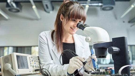 Technikerin löted unter Mikroskop