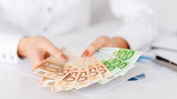 Frau hält Euroscheine in ihren Händen.