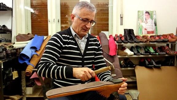 Schumacher Grigore Lup arbeitet an Schuhen in Überlänge