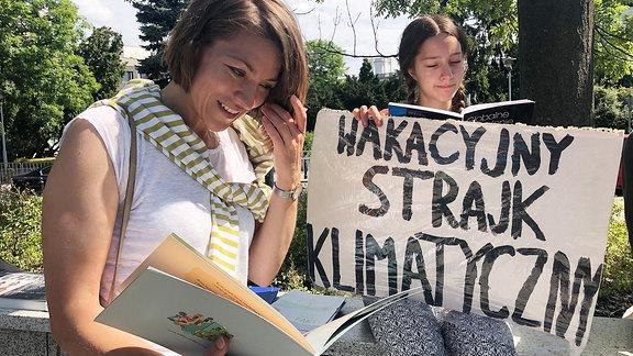 Die junge Umwelt-Aktivistin Inga Zasowska sitzt bei einer Protestaktion neben ihrer Mutter.