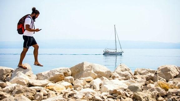 Tourist mit Rucksack geht auf Steinmole entlang, im Hintergrund ein kleines Segelboot.