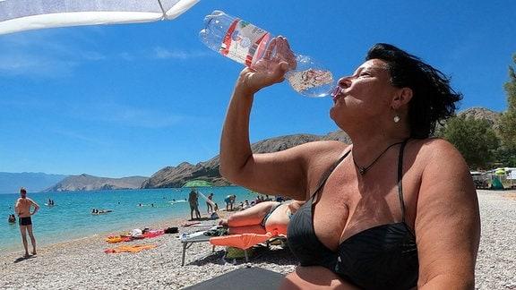 Frau am Stran trinkt aus Wasserflasche.