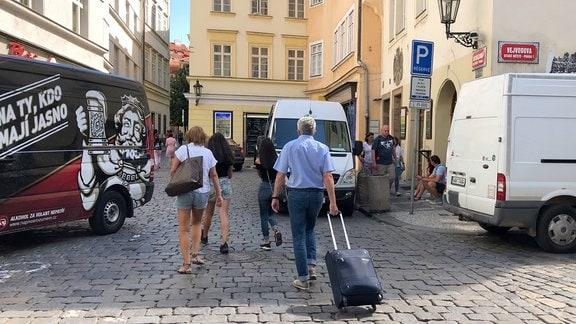 Menschen mit Rollkoffer gehen durch Prager Altstadt
