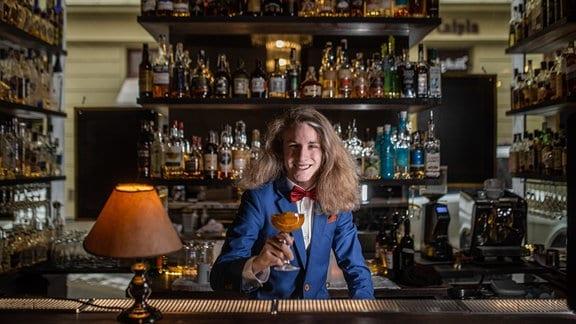 Barkeeper hinter Theke mit Getränk in der Hand
