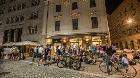 """Gebäude der Kneipe """"Na Stojaka"""" am Abend in Brünn, Menschen und Fahrräder stehen davor"""