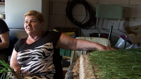 Eine Frau trocknet Büffelgras zu Hause.