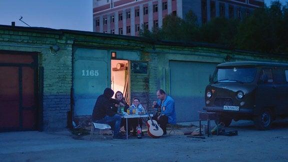 Familie isst vor ihrer Garage