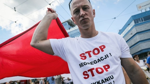 Mann mit polnischer Flagge auf einer Demonstration in Katowice gegen einen Impfzwang in Polen.