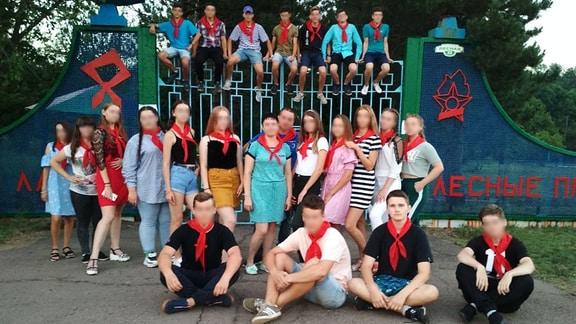 Eine Gruppe Schüler vor einem Eingangstor eines Ferienlagers im Wald. Alle tragen ein rotes Halstuch.