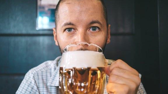 Ein Mann trinkt aus einem Bierglas