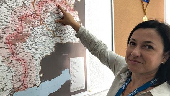 Oleksandra Litwinienko steht vor einer Karte der besetzten Gebiete Luhansk und Donezk.