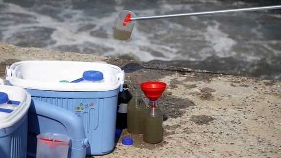 Wasserproben werden aus Fluss entnommen.