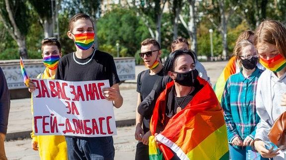 """Ein junger Mann hält ein Schild mit der Aufschrift """"Für uns, für euch, für die LGBTQ im Donbass. Er und einige andere junge Menschen neben ihm tragen Regenbogen-Schutzmasken."""