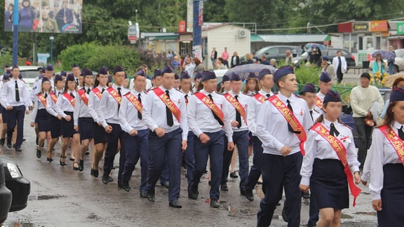 Eine Gruppe von Schülern in Uniform (weißes Hemd bzw. Bluse, dunkelblaues Käppie, schwarze Krawatte bzw. Tuch) marschiert eine Straße im Zentrum von Luhansk entlang.