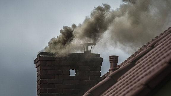 Dunkler Qualm kommt aus einem Schornstein in Luban