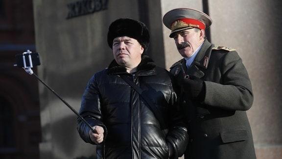 Mann fotografiert sich mit Stalin-Darsteller in Moskau.