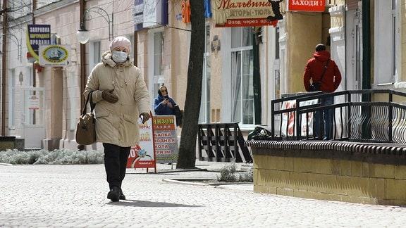 Eine Frau mit Mundschutz läuft auf einer Straße