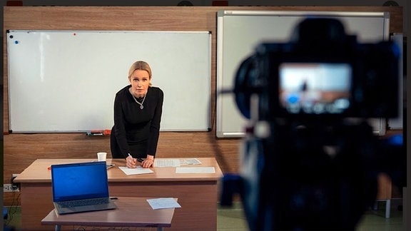 Frau steht an einem Tisch vor einer Tafel und schreibt