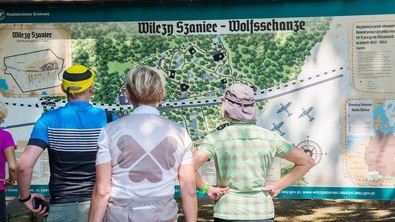 Besucher vor dem Lageplan Adolf Hitlers Kriegsquartiers Wolfsschanze.