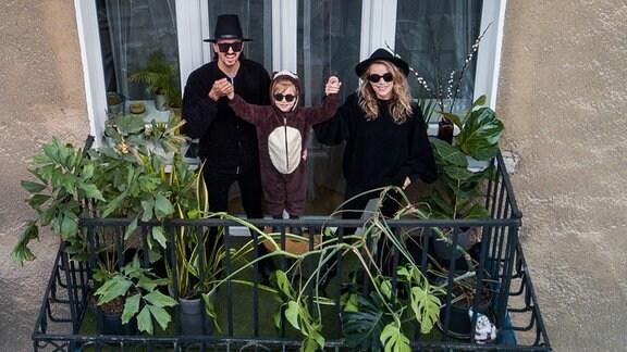 Eine Familie in Kostümen stehen auf dem Balkon