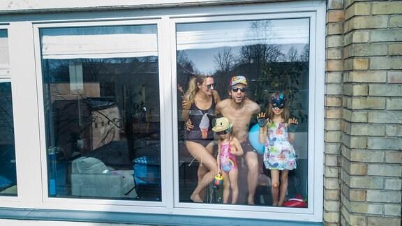 Eine Familie in Badesachen stehen am Fenster