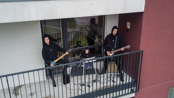 Eine Familie steht mit Istrumenten auf dem Balkon