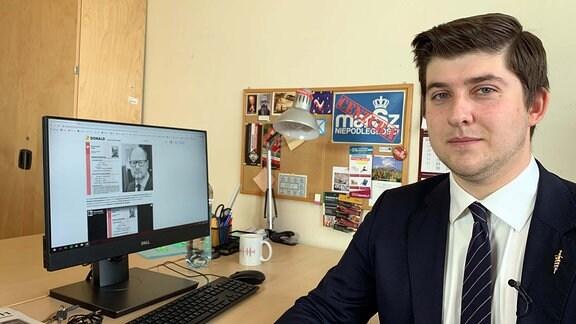 Junger Mann in Anzug sitzt an einem Schreibtisch vor Computer.