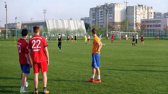 Jugendliche in Trikots stehen auf einem Fußballplatz. Im Hintergrund sozialistische Plattenbauten.
